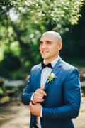 Groom in a blue suit buttoning cuffs Stock Photos