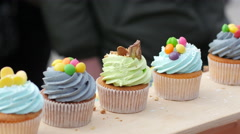 Sweet tasty pastry cupcakes on a street food fair market Stock Footage