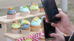 Taking photo picture via phone of sweet pastry cupcakes on a street food fair Stock Footage