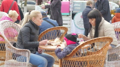 Outdoors people eating at the table on a street festival of food market fair Stock Footage