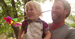 Cheerful dad take his laughing son in his arms outside - stock footage