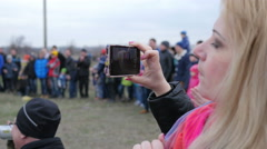 Woman shooting video via smart phone camera of a public performance Stock Footage