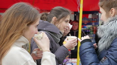Outdoors young teen age girls drinking tea in a street food fair market - stock footage