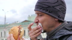 Outdoors food - hunger man eating bites and chews a big tasty burger - stock footage