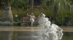 Elderly couple sitting on a bench near the fountain on Place Massena in Nice Stock Footage
