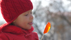 Cute little girl closeup funny licking a sweet lollipop in the shape of heart Stock Footage