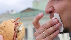 Closeup hunger man eating bites and chews a big burger with cutlet and bacon - stock footage