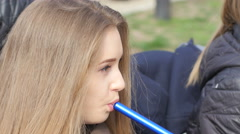 Young pretty girl smoking hookah in a street bar breathing out a smoke - stock footage