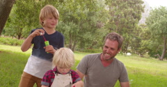 Stock Video Footage of Father and sons having fun with soap bubbles outside