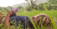Boy enjoys his little bunny lying on grass outside - stock footage