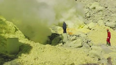 Workers extract sulfur in the crater of the volcano Ijen Stock Footage