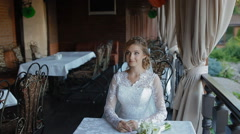 Bride wait sher groom on the summer terrace of cafe Stock Footage