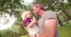 Happy dad kissing his laughing son at the park Stock Footage