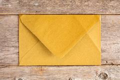 Stock Photo of Golden envelope over  wooden background.