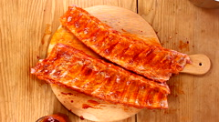 Spare ribs marinating on wooden plate top view Stock Footage