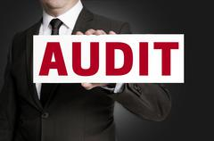 Audit sign is held by businessman background Stock Photos