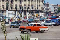 HAVANA, CUBA - APRIL 1, 2012: Heavy traffic with taxi bikes and vintage cars - stock photo