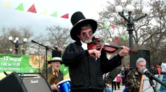 Busker hat bowler hat and round black glasses playing the violin. Stock Footage