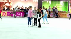 Young children learn to skate on the ice rink. - stock footage