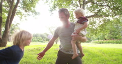 Modern dad takes his two children in his arms Stock Footage
