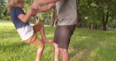 Cheerful dad playing with his boy at the park - stock footage