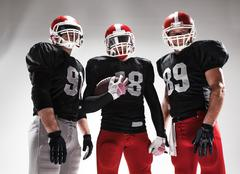 The three american football players posing with ball on white background - stock photo