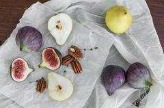 Figs, pears and pekan nuts on a white tissue on a wooden table surface - stock photo