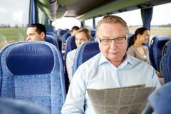 happy senior man reading newspaper in travel bus - stock photo