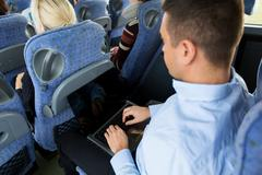 Man with smartphone and laptop in travel bus Stock Photos
