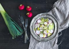Spring salad with leek, radish and cucumber in vintage metal plate - stock photo