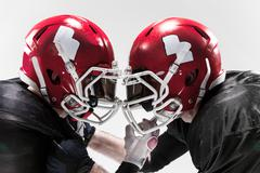 The two american football players fighting on white background - stock photo