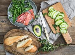 Stock Photo of Salmon and avocado sandwiches with fresh thyme in baguette tied up with a dec