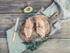 Salmon and avocado sandwiches with fresh thyme in baguette tied up with a dec Stock Photos
