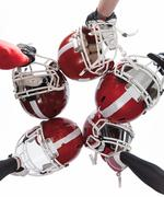 The hands of american football players with helmets on white background - stock photo