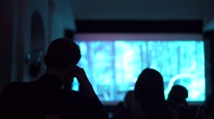 Silhouettes of people watching movie in dark cinema hall - stock footage