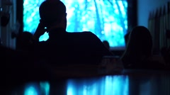 Silhouettes of unrecognizable people watching movie in dark cinema hall - stock footage