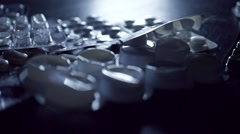 Drug blister packs fall on dark table. 2 slow motion shots in 1 Stock Footage