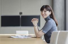 Portrait confident businesswoman with paperwork in conference room Stock Photos