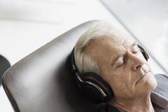 Senior man with headphones listening to music and reclining - stock photo