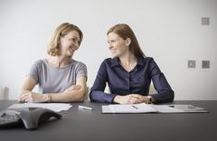 Smiling businesswomen talking in meeting - stock photo