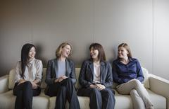 Smiling businesswomen talking in a row on sofa - stock photo