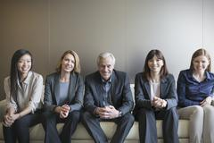 Portrait smiling business people in a row on sofa - stock photo