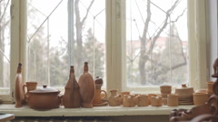 Pots in the window of a potter's workshop, a traditional pottery. RAW video Stock Footage