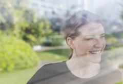 Stock Photo of Smiling woman looking out window