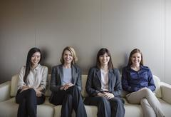 Stock Photo of Portrait smiling businesswomen sitting in a row on sofa