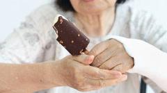 Elderly woman broken wrist enjoying ice cream Stock Footage