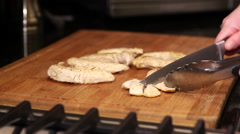 Chicken being cut on wooden cutting board Stock Footage