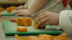 Culinary School - Students cutting up carrots for their professor Stock Footage