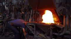 Blacksmith working iron on a forge with fire - stock footage