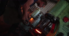 Mechanical hammering of glowing iron in blacksmith forge - stock footage